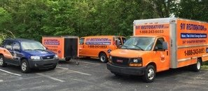 Water and Mold Damage Restoration Trucks, Van And Trailer On Job Site